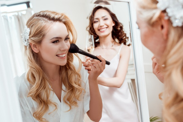 beautiful young bride getting makeup before wedding and looking at mirror