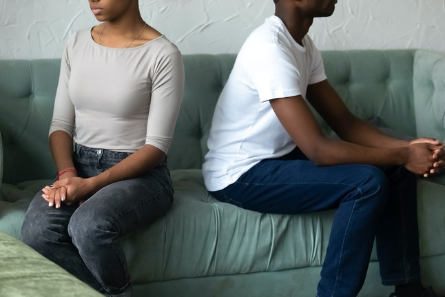Crop close up of african American husband and wife sit separately back to back on couch avoid talking after fight, stubborn black couple ignore not looking at each other. Divorce or split concept
