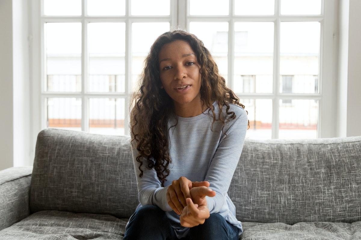 Serious friendly african woman internet teacher tutor looking at camera talking, black mixed race mi...