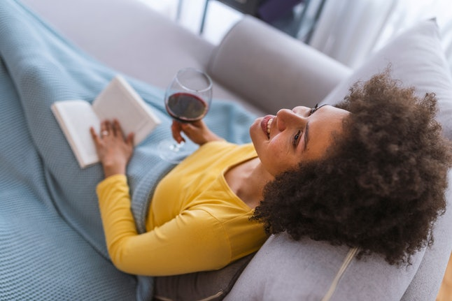 Relaxed young woman reading a book. Domestic life. Relaxed young lady is reading, lying on the cozy beige couch in living room at home, so nice modern interior, so comfortable atmosphere