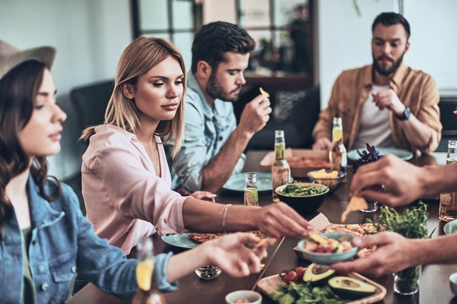 Just hungry. Group of young people in casual clothing eating while having a dinner party indoors