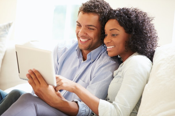 Young Couple Sitting On Sofa Using Digital Tablet