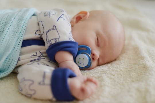 newborn with dummy sleeping on the bed