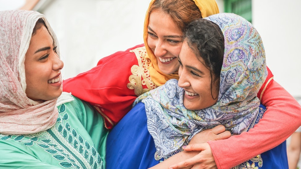 Young islamic friends having fun outdoor - Happy arabian friends laughing and smiling together - Friendship, religion, ethnic culture and youth concept - Focus on top girl face
