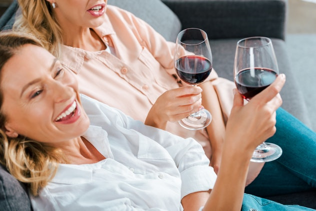 cropped shot of mature mother and adult daughter with glasses of red wine spending time together at ...