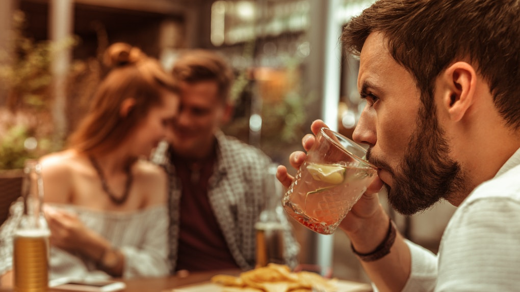 Feeling like the third wheel. Close-up face portrait of dark-haired bearded handsome young-adult man lonely sipping a cocktail while his mates hugging each other