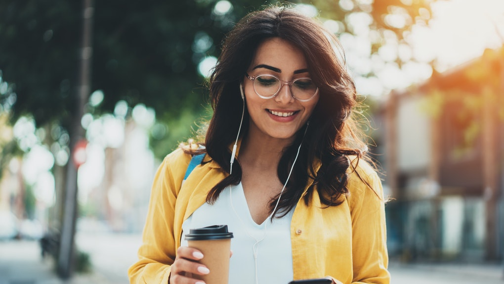 Lifestyle portrait of happy woman walking in the city on a sunny summer day, beautiful young girl dressed in casual style listening to music and typing text message on smartphone device, flare light