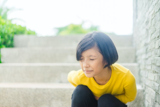 Healthcare medical in Teenager concept : First period in Pre Teenager girl at school, She have a stomachache or menstruation pain or period pain sitting on a stairs.