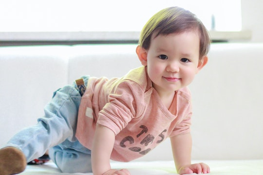 Crawling baby boy smiling at home. Healthy adorable mixed race Asian-German kid wearing red T-shirt and  blue jeans
