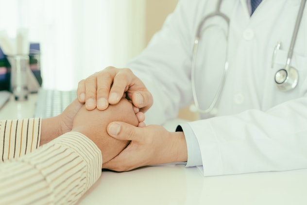 Friendly man doctor hands holding patient hand sitting at the desk for encouragement, empathy, cheer...