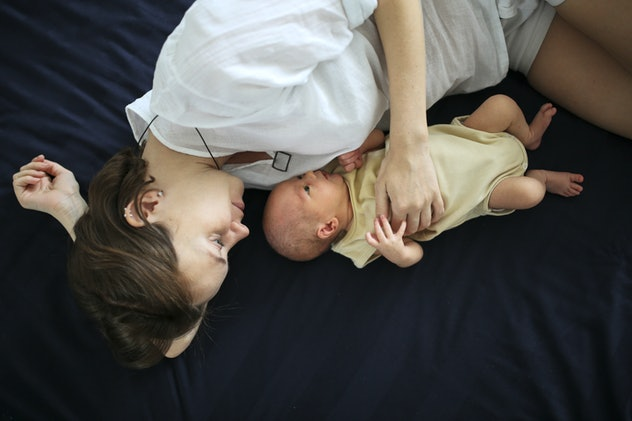 newborn with mom on a dark sheet, baby and mother on the bed, concept of motherhood