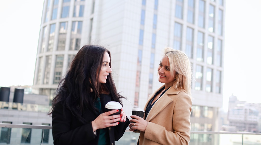 two women walk in the city, drink coffee and enjoy the rest