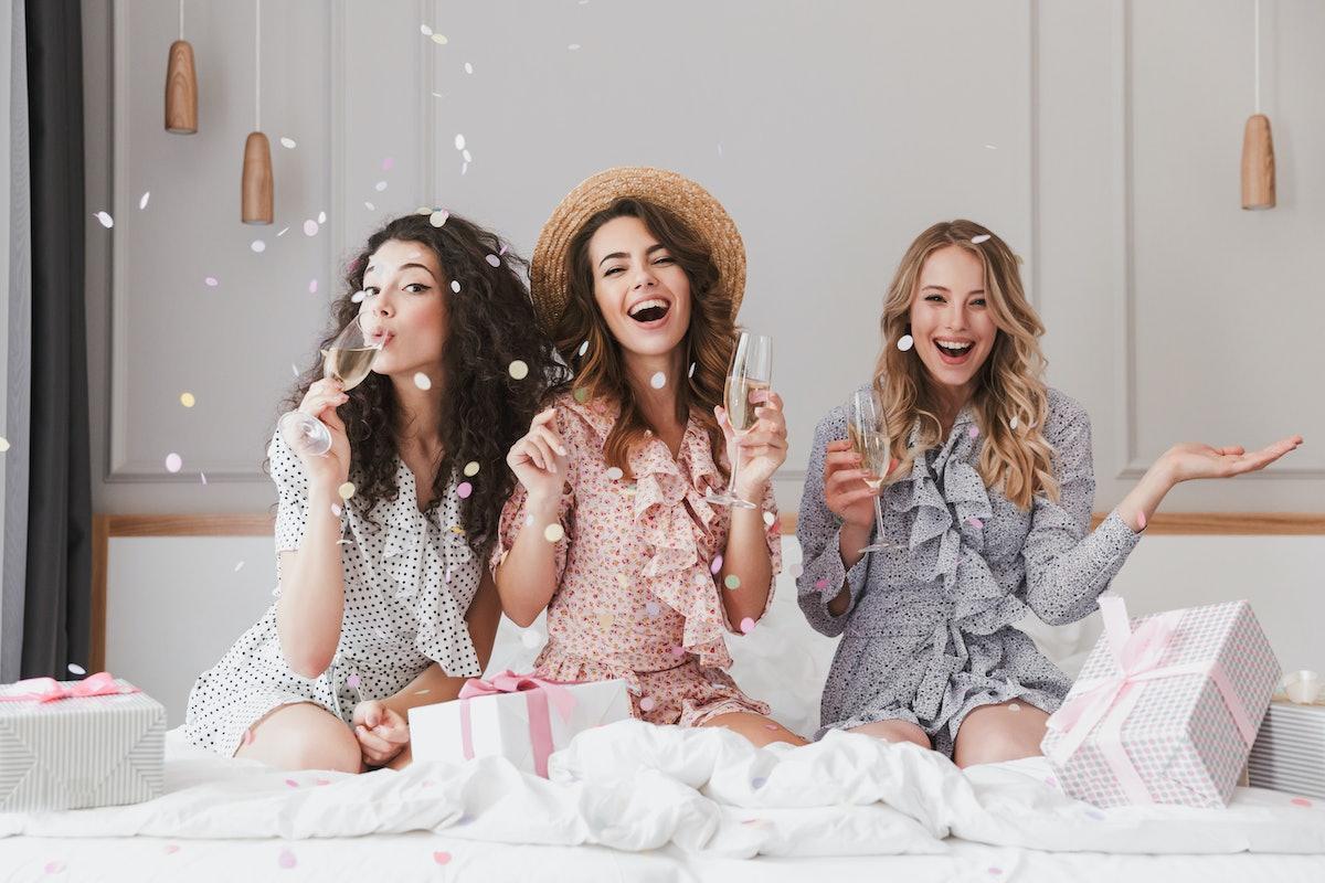 Image of caucasian stylish women 20s wearing dresses celebrating bachelorette party in fashion apart...