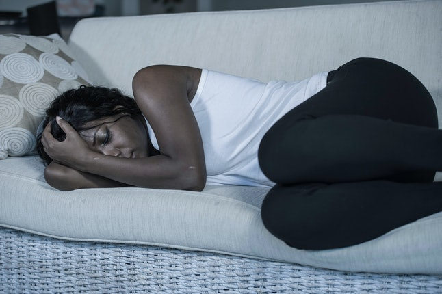 young attractive and sad black African American woman lying depressed at home sofa couch feeling anxious and frustrated suffering depression problem and anxiety crisis or terrible headache