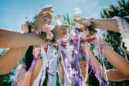 The hands of girls with boutonnieres and ribbons hold and raise glasses of champagne up. champagne glass decorated with flowers. Party in Style boho. Maiden evening Hen-parties. Bachelorette. Close up
