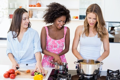 Friends preparing a meal together in kitchen at home