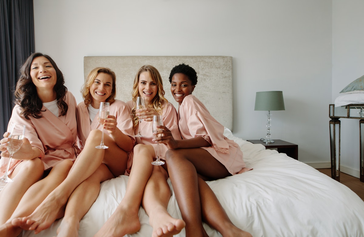 Bride and bridesmaids celebrating bachelorette party in bedroom. Happy females friends sitting on be...