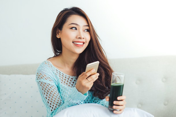 Smiling young asian woman drinking green fresh vegetable juice or smoothie from glass using smartphone at home