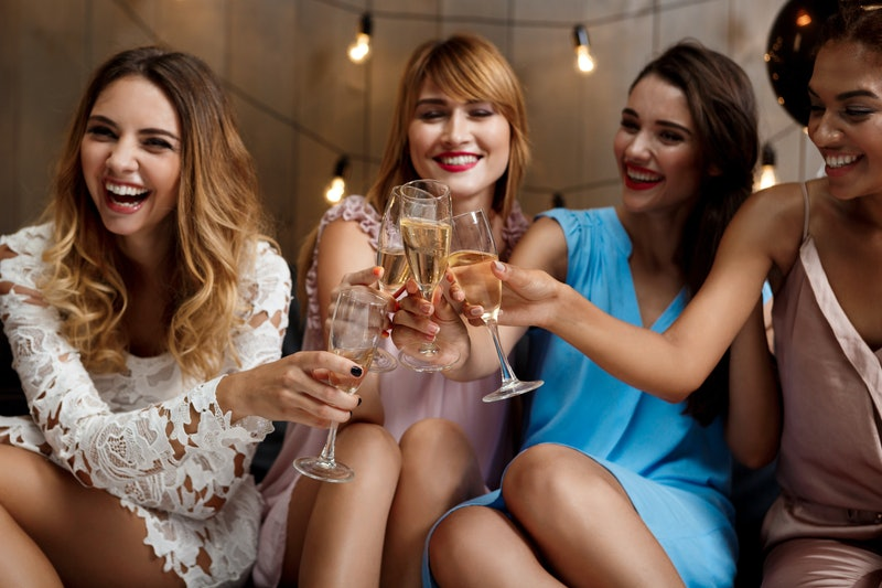 Four beautiful girls clinking glasses with champagne at party.