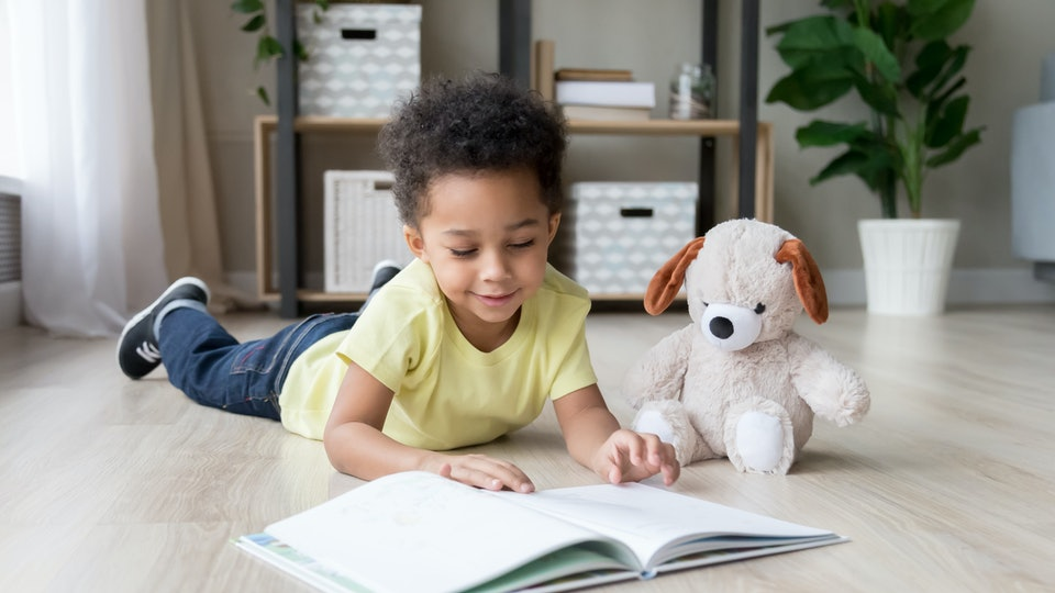 Adorable toddler mixed race boy reading book at home or in kindergarten, beautiful preschooler child with toy lying on warm floor, playing, having fun, kid and study, education concept