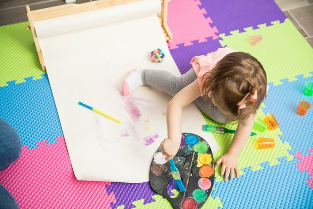 Top view of a beautiful girl learning painting skills sitting on her bedroom floor