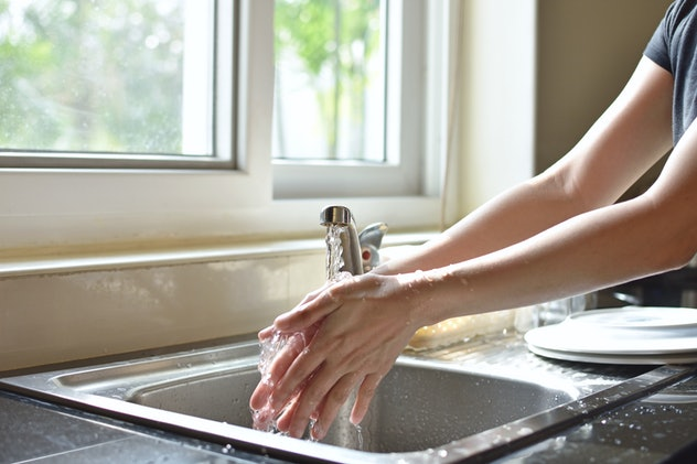 Close Up Of Woman Washing Hands In Kitchen Sink
