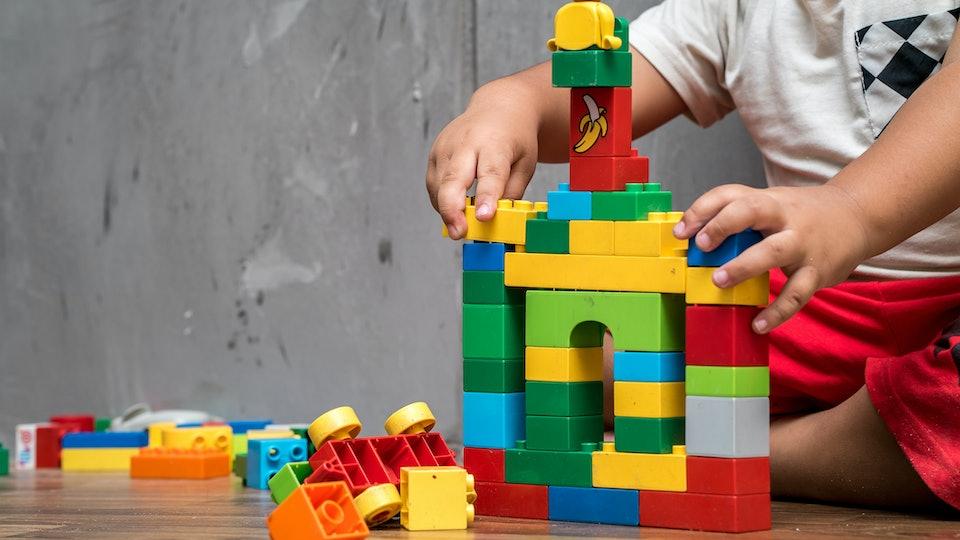 Asian kid boy building house from plastic blocks
