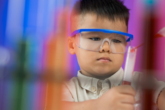 Blurred image of a young researcher dropping in the test-tube on the foreground