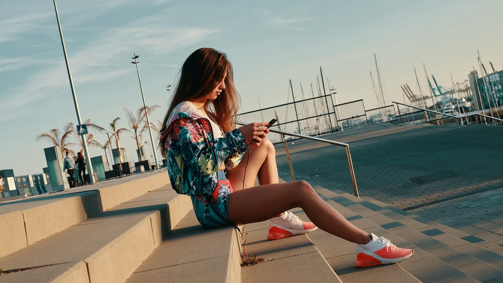 Texting to friend. Attractive young woman in sports clothing using smart phone while sitting on the steps outdoors
