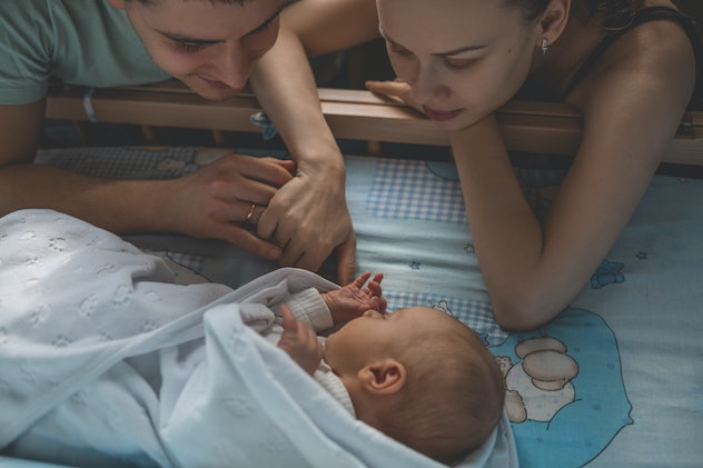 Woman and man look at newborn. Boy sleeps in his crib. Mom, dad and baby. Portrait of young family. Happy family life. Man was born. Horizontally framed shot.