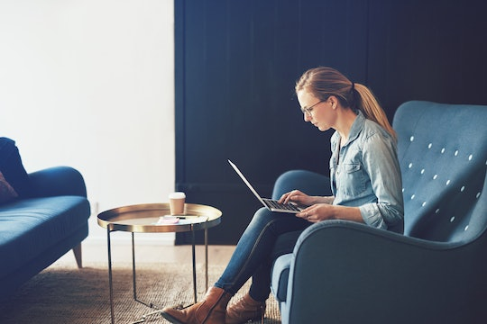 Smiling young businesswoman browsing online with a laptop while sitting on a sofa in a modern office