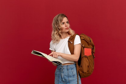Confused blond girl with curly hair in a white t-shirt trying to find itinerary with the map holding brown orange backpack. Girl lost at the unknown place. Concept of travel