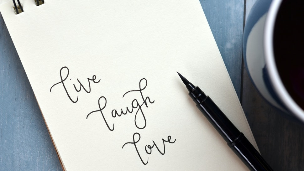 LIVE LAUGH LOVE written in notepad on blue wooden background with cup of coffee and pen