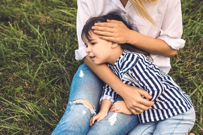 Cropped image of cute little girl embrace her mother outdoor. Loving mother and daughter lying on the green grass in the park. Mom and kid cuddling and have fun outside. Good relationship together.