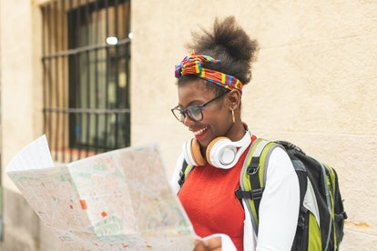 Afro American Girl Traveling Alone and Using a Map. Afro Teenager Girl Traveling Alone ,Wearing Headphones and Smiling. Travel Concept.
