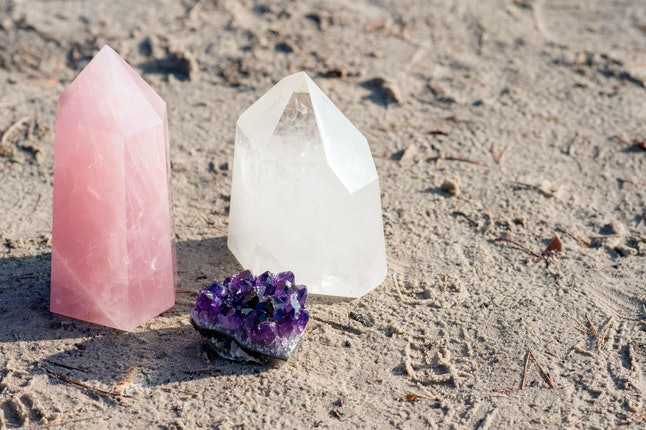 Golden Triangle gemstones: amethyst, rose quartz and white quartz, standing together on the beach
