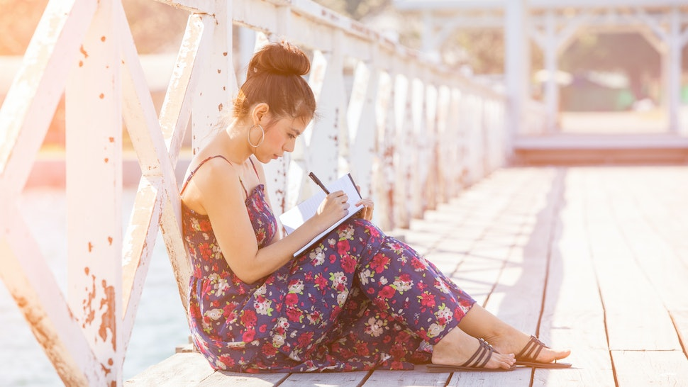 Woman writing by pen in notepad at sunny summer