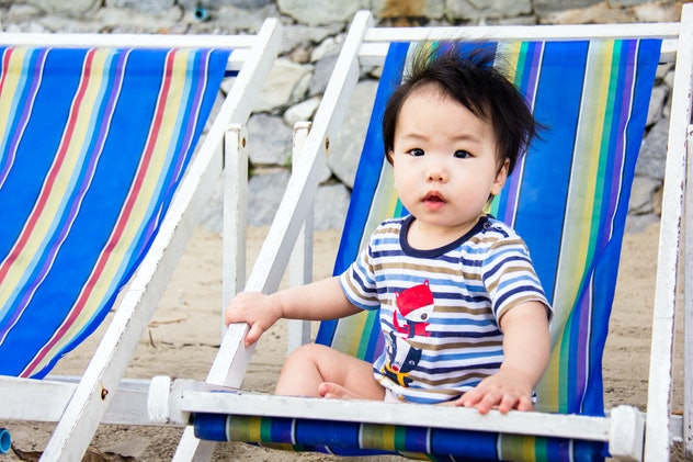 A little baby is enjoy sitting on the colorful beach chair at the seacoast. Grey stone wall backgrou...