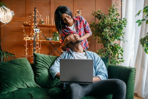 Black couple with laptop having fun on sofa