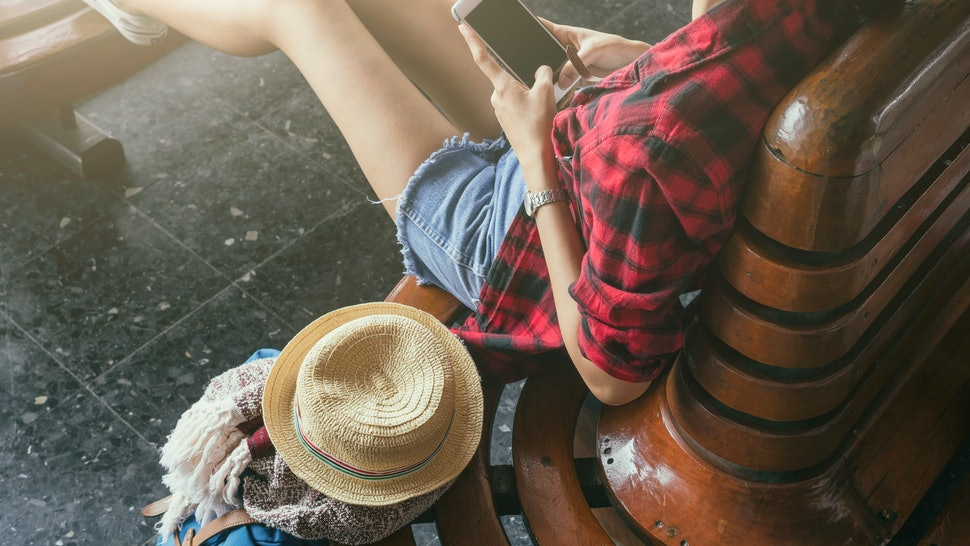Woman traveler holding smart phone on wood chair with travel accessories,travel accessories concept such as bag hat camera scarf and gadget,Woman wear red shirt,flare effect and vintage tone.