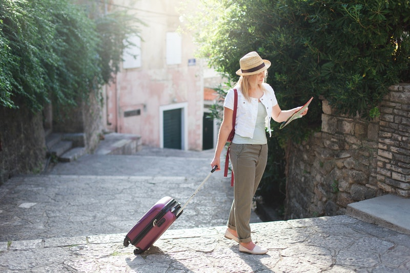 Girl traveler looks at city map with suitcase at town street in Europe. Woman tourist is searching apartment, house. Concept of travel, summer vacation, solo female tourism, adventure, trip, journey