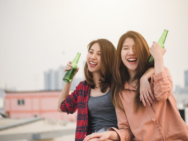Young asian woman lesbian couple clinking bottles of beer party on rooftop.