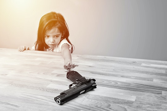 safety and accident in home concept. children try to play parent's gun on table. monotone color