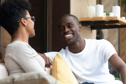 Happy african American millennial man and woman sit in coffee shop have fun talking or flirting, smiling black couple hang out together in cafe chat having pleasant conversation. Friendship concept