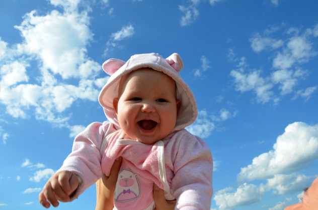 baby and sky in the background on a sunny day. Young handsome father holding up his little cute daug...