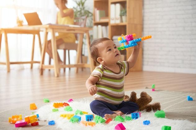 Vietnamese baby boy playing with plastic blocks