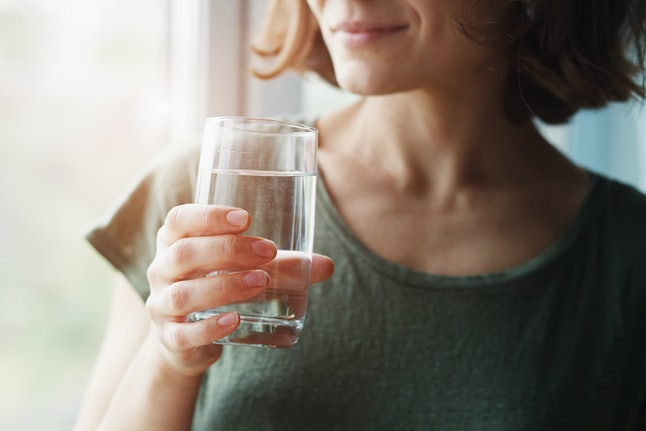Young woman holding a glass of water, one of the best natural remedies for constipation