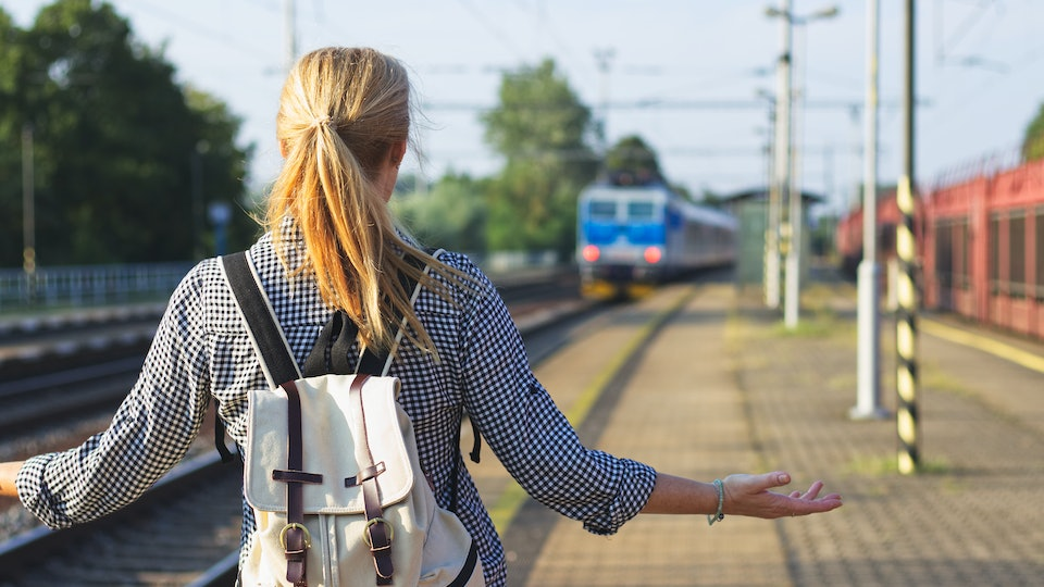 I am late! Woman standing on railroad station and looking to leaving train. Traveler is worried, because she missed a train