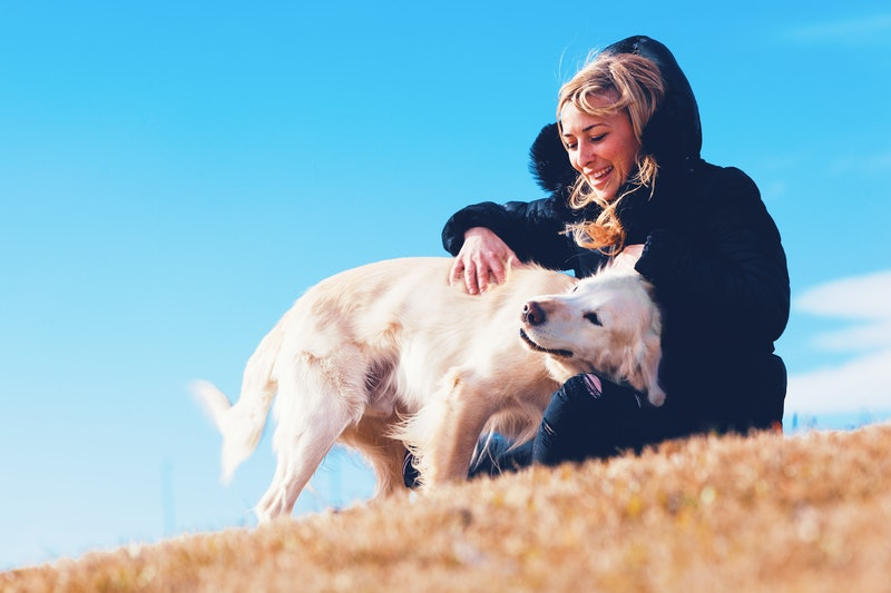 Pets and dogs.Blonde girl smiling and enjoying her pet dog in the park.