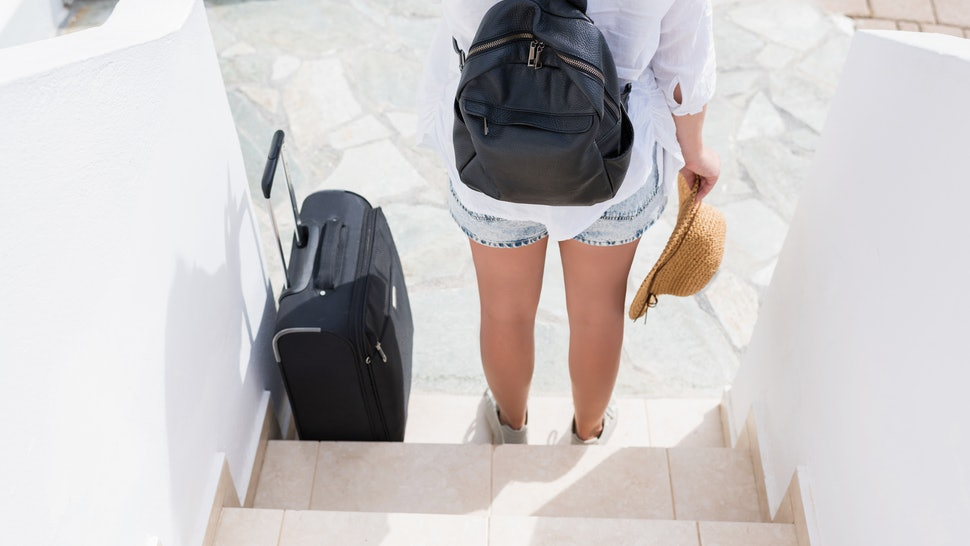 woman with suitcase waiting the owners of the apartment for check - in. Individual traveler.